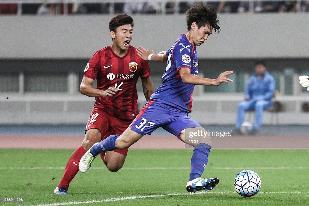 Li Haowen #12 of Shanghai SIPG and <a gi-track='captionPersonalityLinkClicked' href=/galleries/search?phrase=Kento+Hashimoto&family=editorial&specificpeople=9967864 ng-click='$event.stopPropagation()'>Kento Hashimoto</a> #37 of FC Tokyo compete for the ball during the 1/8 match of AFC Asia Champions League between Shanghai SIPG and FC Tokyo at Shanghai Stadium on May 24, 2016 in Shanghai, China.