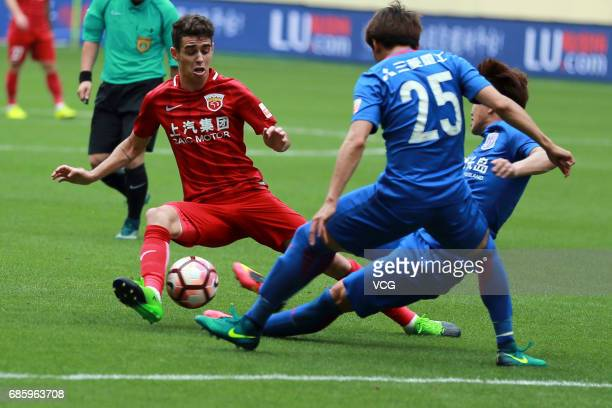 Li Jianbin of Shanghai Shenhua and Oscar of Shanghai SIPG compete for the ball during the 10th round match of CSL Chinese Football Association...