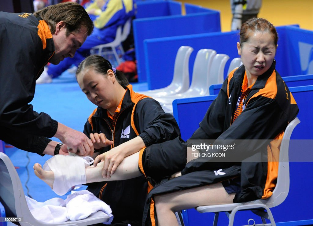 <a gi-track='captionPersonalityLinkClicked' href=/galleries/search?phrase=Li+Jie+-+Table+Tennis+Player&family=editorial&specificpeople=12783702 ng-click='$event.stopPropagation()'>Li Jie</a> (R) of the Netherlands reacts as a Dutch trainer (L) and player Li Jiao (C) attend to her injured foot during Li's quarter-final match against Singapore at the World Team Table Tennis Championships in Guangzhou, in China's Guangdong province on February 28, 2008. Singapore were leading their quarter-final clash with the Netherlands 2-0 when <a gi-track='captionPersonalityLinkClicked' href=/galleries/search?phrase=Li+Jie+-+Table+Tennis+Player&family=editorial&specificpeople=12783702 ng-click='$event.stopPropagation()'>Li Jie</a> twisted her ankle in the opening game of the crucial third match, forcing the Europeans to abandon the encounter.