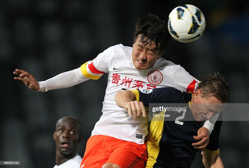 Li Kai of Guizhou Renhe heads the ball over <a gi-track='captionPersonalityLinkClicked' href=/galleries/search?phrase=Daniel+McBreen&family=editorial&specificpeople=2229191 ng-click='$event.stopPropagation()'>Daniel McBreen</a> of the Mariners during the AFC Asian Champions League match between the Central Coast Mariners and Guizhou at Bluetongue Stadium on April 3, 2013 in Gosford, Australia.