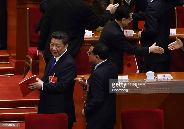 Li Keqiang China's premier second left speaks with Xi Jinping China's president left after the closing session of the third session of the 12th...