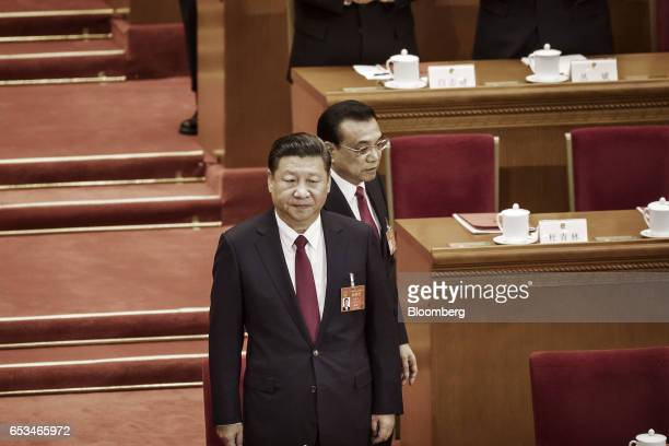 Li Keqiang China's premier walks behind Xi Jinping China's president during the closing ceremony of the National People's Congress in Beijing China...
