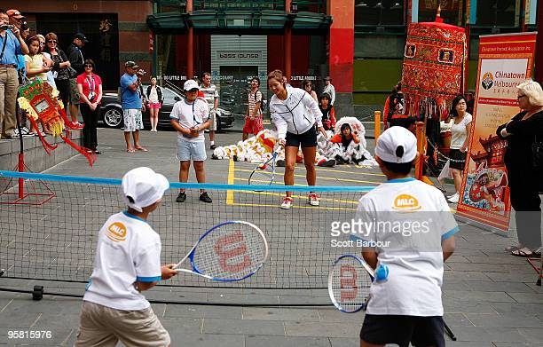 Li Na of China plays a game of tennis with children from the MLC Tennis Hot Shots program on a mini court while she visits Melbourne's Chinatown...