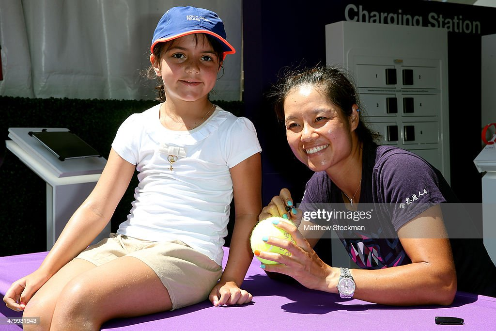 Li Na of China poses for pictures and signs autographs at the Sony booth during the Sony Open at the Crandon Park Tennis Center on March 21, 2014 in Key Biscayne, Florida.