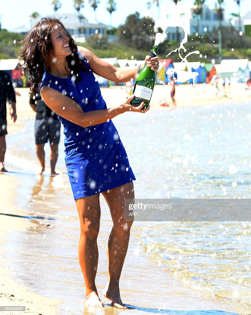 Li Na of China poses with champagne following her victory over Dominika Cibulkova of Slovakia in the women's singles final on day 14 of the 2014 Australian Open tennis tournament at the bathing huts on Brighton Beach in Melbourne on January 26, 2014. IMAGE