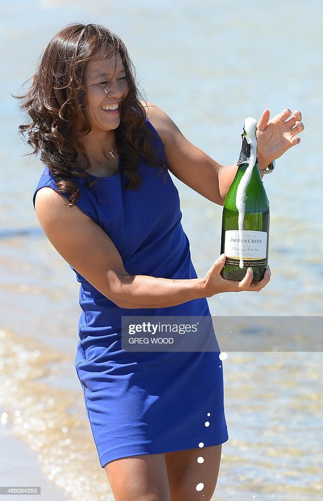 Li Na of China uncorks a champagne bottle as she poses following her victory over Dominika Cibulkova of Slovakia in the women's singles final on day 14 of the 2014 Australian Open tennis tournament at Brighton Beach in Melbourne on January 26, 2014. IMAGE