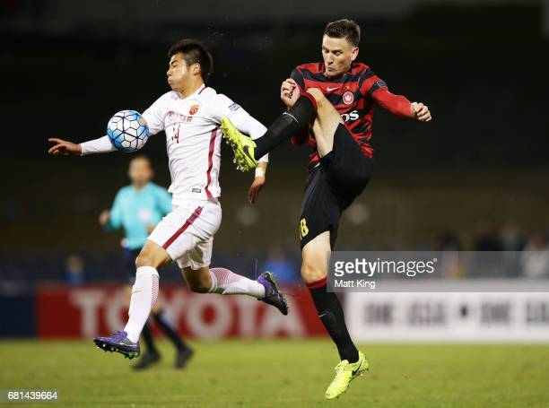 Li Shenglong of Shanghai is challenged by Robbie Cornthwaite of the Wanderers during the AFC Asian Champions League Group Stage match between the...