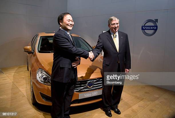 Li Shufu chairman of Zhejiang Geely Holding Co left and Lewis Booth chief financial officer at Ford Motor Co shake hands at the start of a news...