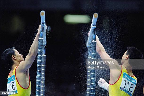 Li Xiaoshuang and Zhang Jingjin of China prepare for their Parallel Bars routine of the Men's Individual AllAround at the XXVI Summer Olympic Games...