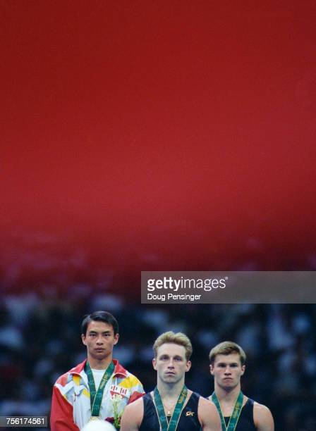 L R Li Xiaoshuang of China stands on the podium with his gold medal alongside bronze medallist Vitaly Scherbo and silver medallist Alexei Nemov after...