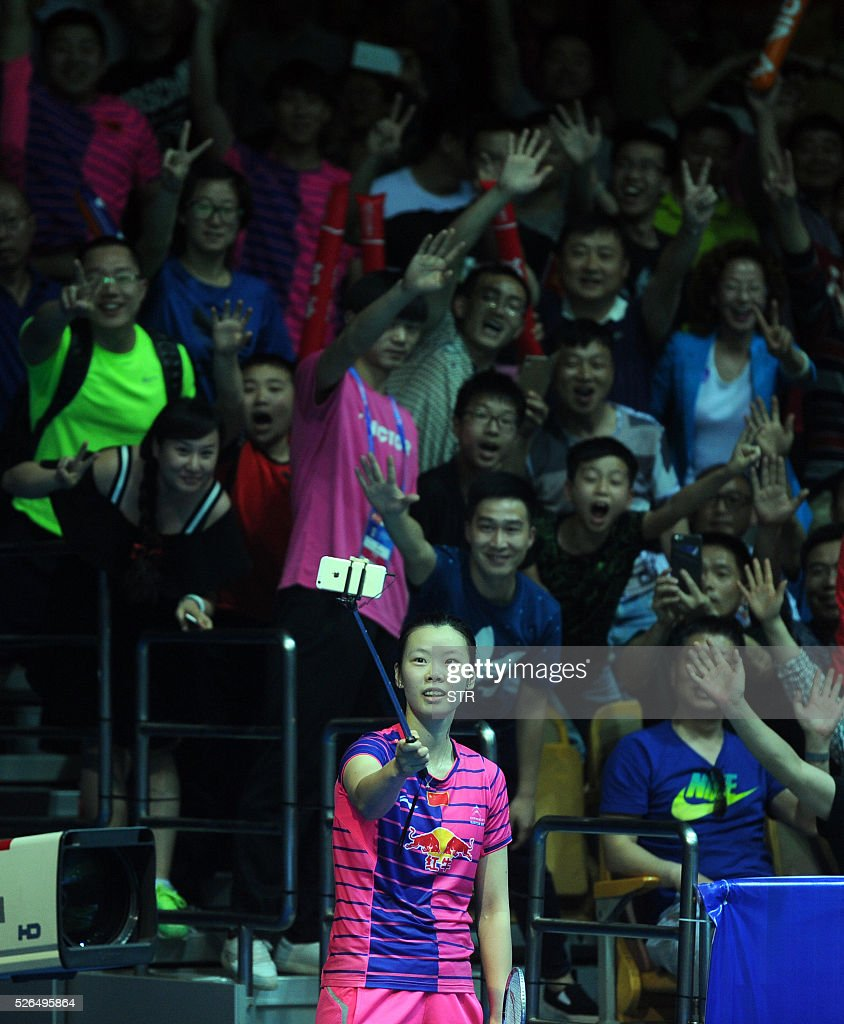 Li Xuerui of China uses a selfie stick to take photos with supporters after winning the women's singles semi-final match against Sung Ji Hyun of South Korea at the 2016 Badminton Asia Championships in Wuhan, central China's Hubei province on April 30, 2016. / AFP / STR