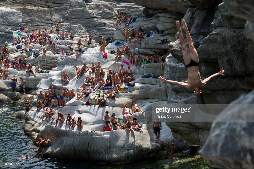 Liam Atkins of Australia dives from a 20 metre rock as spectators watch on during the Cliff Diving European Championship on July 19, 2014 in Ponte Brolla near Locarno, Switzerland.