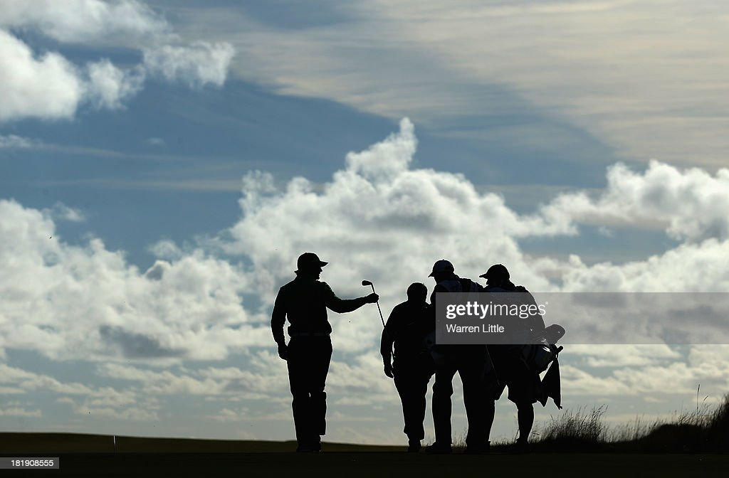 Liam Botham of England hands his caddie his club during the first round of the Alfred Dunhill Links Championship at Kingsbarns on September 26, 2013 in Kingsbarns, Scotland.