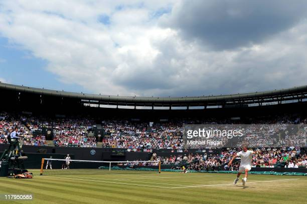 Liam Broady of Great Britain and Luke Saville of Australia play for a near capacity Court 1 crowd during their final round boy's match on Day Twelve...