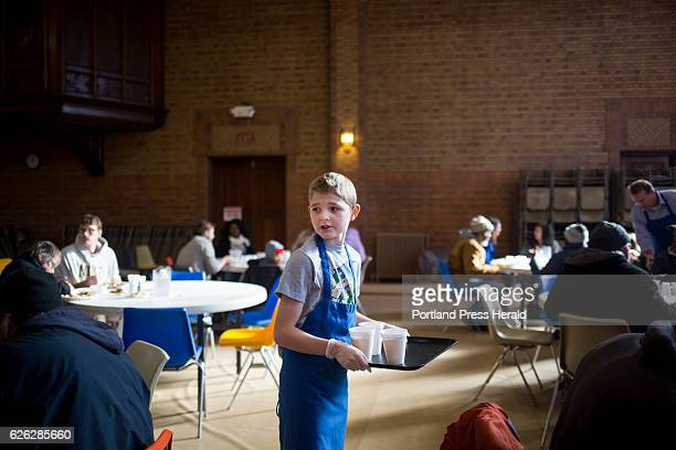 Liam Curran of Falmouth serves juice and milk to patrons at the St Vincent DePaul soup kitchen's Thanksgiving dinner Curran's father is part of the...