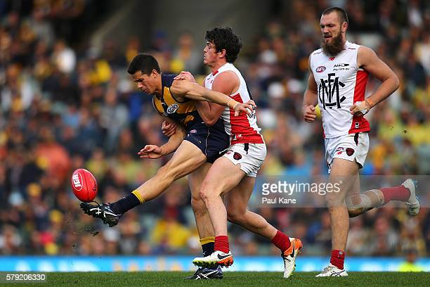 Liam Duggan of the Eagles gets his kick away while being tackled by Angus Brayshaw of the Demons during the round 18 AFL match between the West Coast...