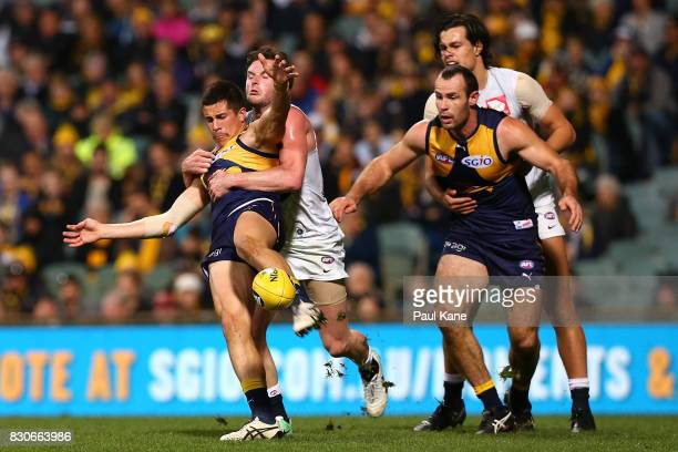 Liam Duggan of the Eagles gets his kick away while being tackled by Jed Lamb of the Blues during the round 21 AFL match between the West Coast Eagles...