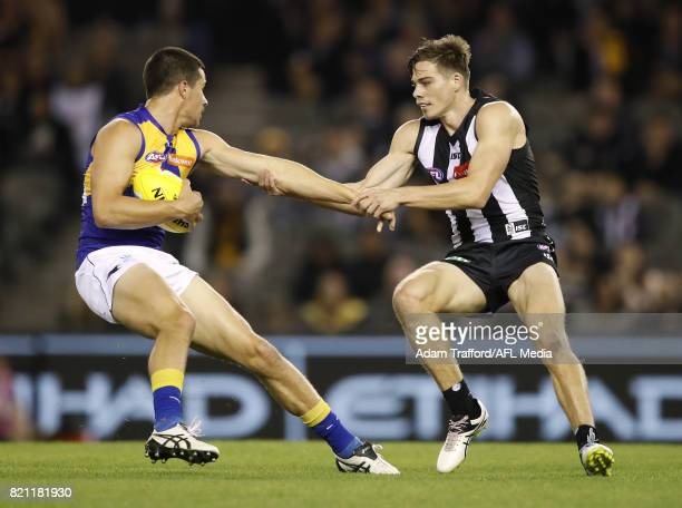 Liam Duggan of the Eagles is tackled by Josh Thomas of the Magpies during the 2017 AFL round 18 match between the Collingwood Magpies and the West...