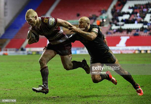 Liam Farrell of Wigan Warriors beats Glenn Stewart of Catalans Dragons on his way to scoring a disallowed try during the First Utility Super League...