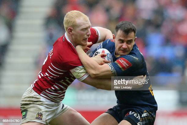 Liam Farrell of Wigan Warriors tackles Ryan Morgan of St Helens during the Betfred Super League match between Wigan Warriors and St Helens at DW...