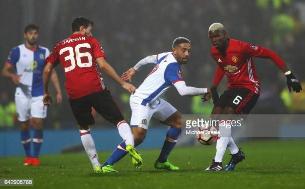Liam Feeney of Blackburn Rovers goes between Matteo Darmian and Paul Pogba of Manchester United during The Emirates FA Cup Fifth Round match between...