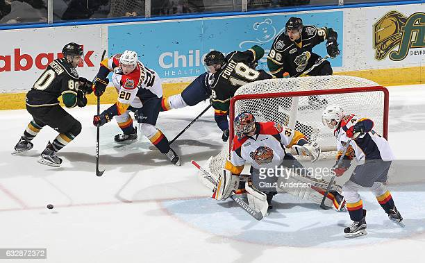 Liam Foudy and Alex Formenton of the London Knights look to grab a shot at Troy Timpano of the Erie Otters during an OHL game at Budweiser Gardens on...
