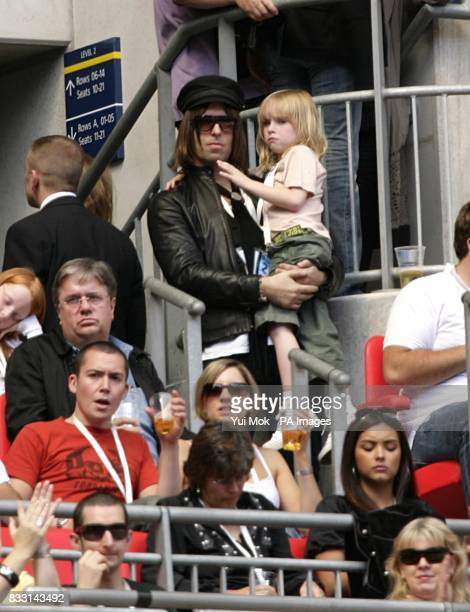 Liam Gallagher observes from the stands with his son Lennon during the charity concert at Wembley Stadium London