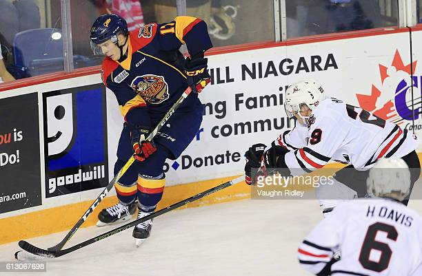 Liam Ham of the Niagara IceDogs and Taylor Raddysh of the Erie Otters battle for the puck during the second period of an OHL game at the Meridian...