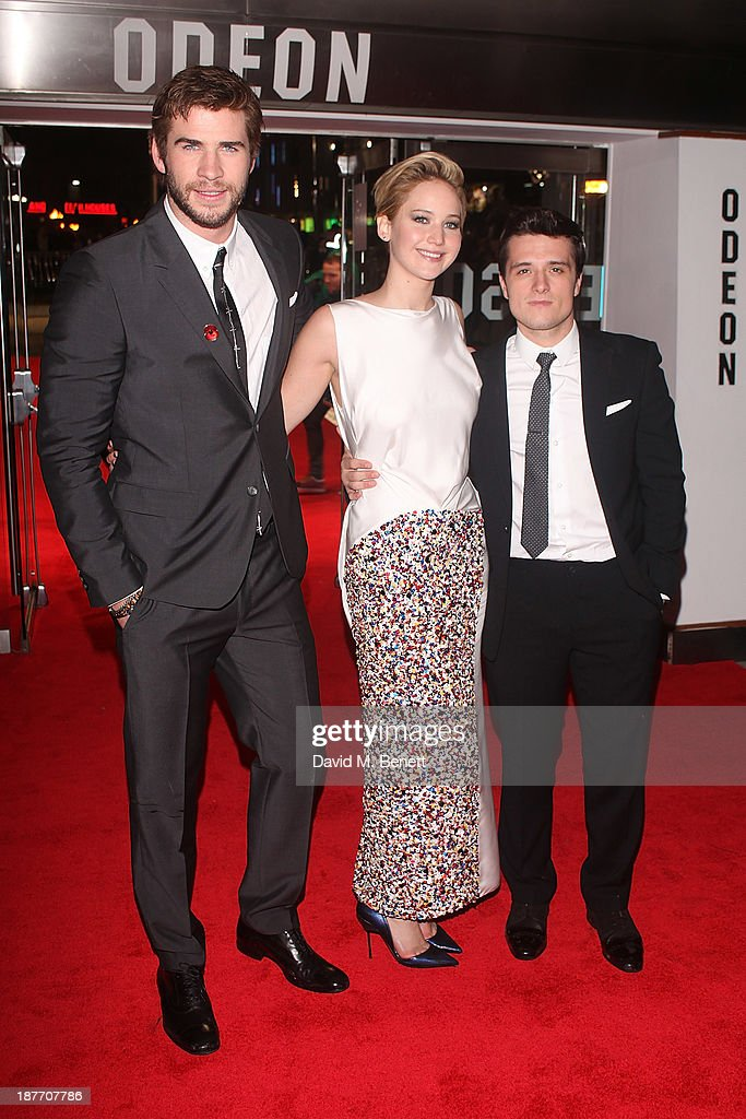 Liam Hemsworth, Jennifer Lawrence and Josh Hutchinson attend the UK Premiere of 'The Hunger Games: Catching Fire' at Odeon Leicester Square on November 11, 2013 in London, England.