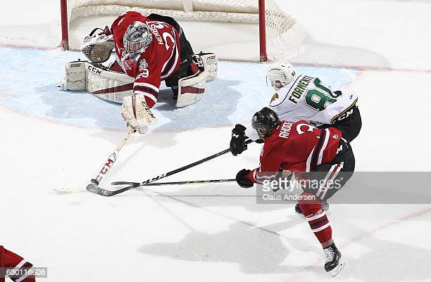 Liam Herbst of the Guelph Storm knocks the puck away from Alex Formenton of the London Knights during an OHL game at Budweiser Gardens on December 16...