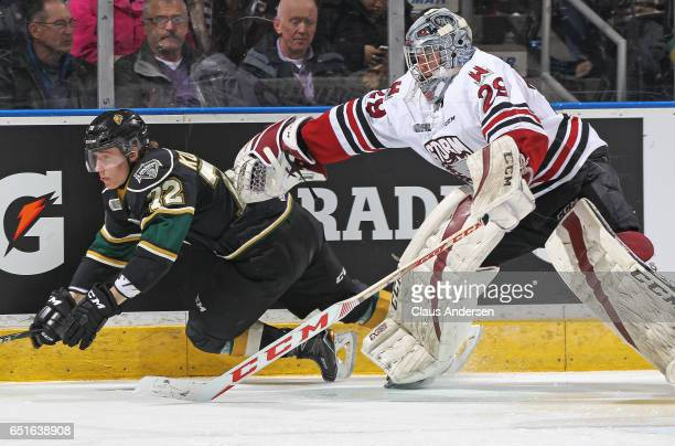 Liam Herbst of the Guelph Storm trips up Janne Kuokkanen of the London Knights during an OHL game at Budweiser Gardens on March 9 2017 in London...