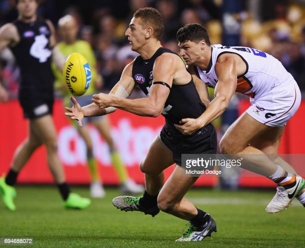 Liam Jones of the Blues handballs away from Jonathon Patton of the Giants during the round 12 AFL match between the Carlton Blues and the Greater...