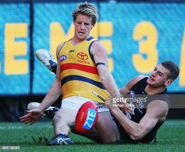 Liam Jones of the Blues tackles Rory Sloane of the Crows during the round 15 AFL match between the Carlton Blues and the Adelaide Crows at Melbourne...