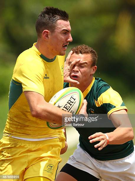 Liam McNamara of Australia fends off a tackle during the Rugby Sevens Men's Final match between Australia and South Africa at the Apia Park Sports...