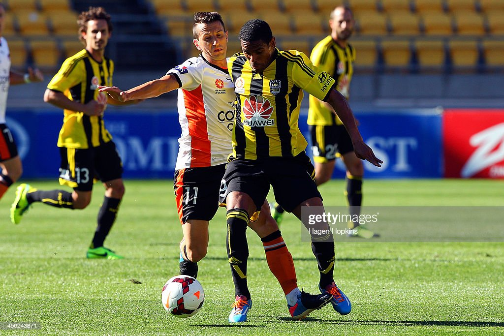Liam Miller of the Roar and Kenny Cunningham of the Phoenix compete for the ball during the round 10 A-League match between the Wellington Phoenix and Brisbane Roar at Westpac Stadium on December 14, 2013 in Wellington, New Zealand.