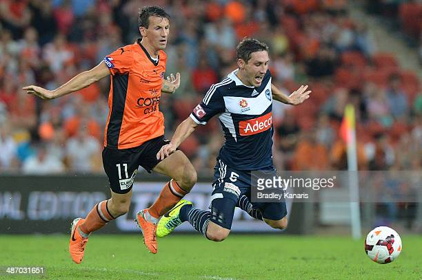 Liam Miller of the Roar is penalised for this challenge on Mark Milligan of the Victory during the ALeague Semi Final match between the Brisbane Roar...