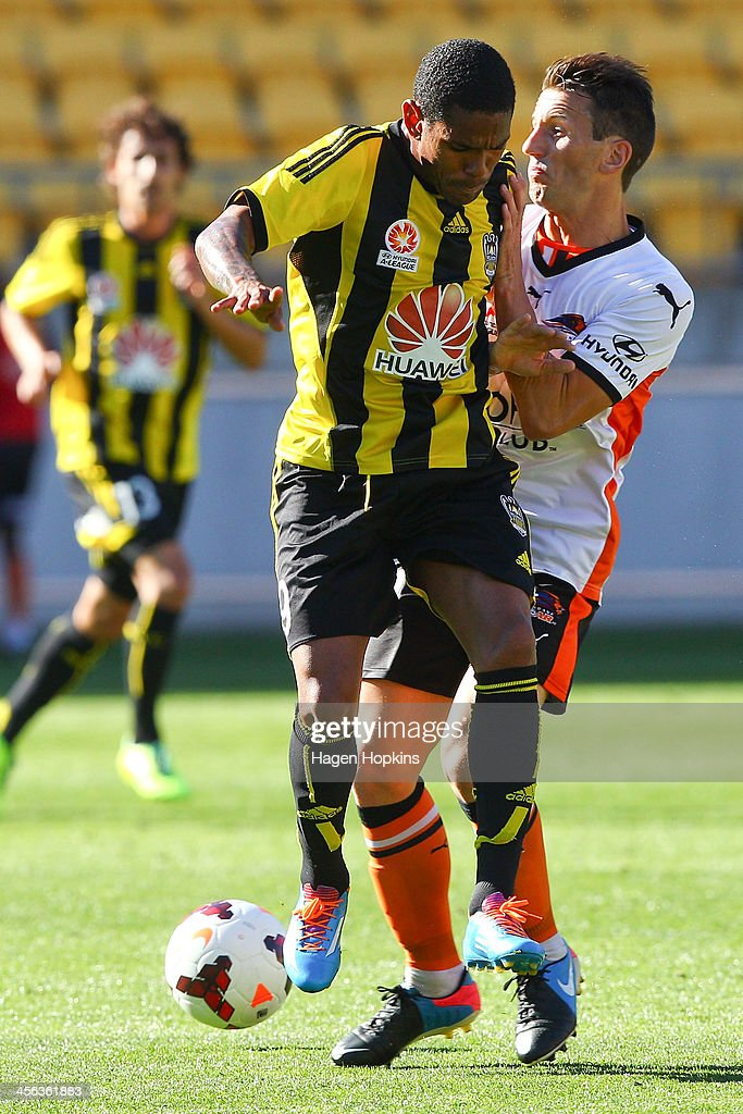 Liam Miller of the Roar tackles Kenny Cunningham of the Phoenix during the round 10 A-League match between the Wellington Phoenix and Brisbane Roar at Westpac Stadium on December 14, 2013 in Wellington, New Zealand.