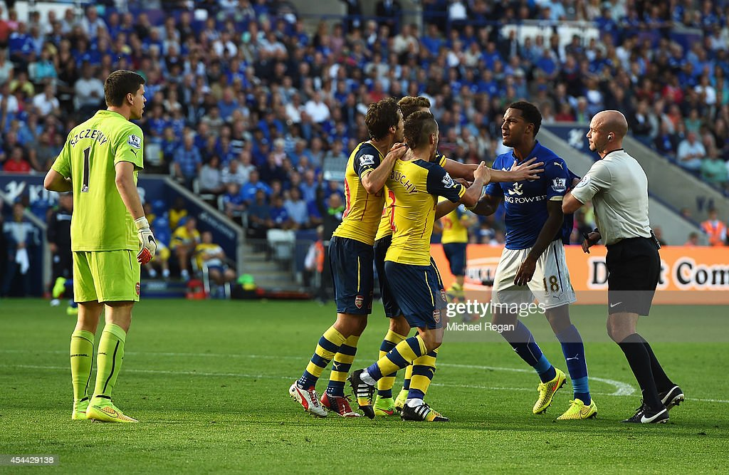 Liam Moore of Leicester City is held back after a challenge on Wojciech Szczesny of Arsenal during the Barclays Premier League match between Leicester City and Arsenal at The King Power Stadium on August 31, 2014 in Leicester, England.