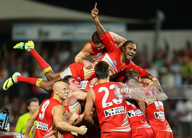 Liam Patrick of the Suns celebrates with Karmichael Hunt and team mates after Hunt kicked the match winning goal after the final siren during the...
