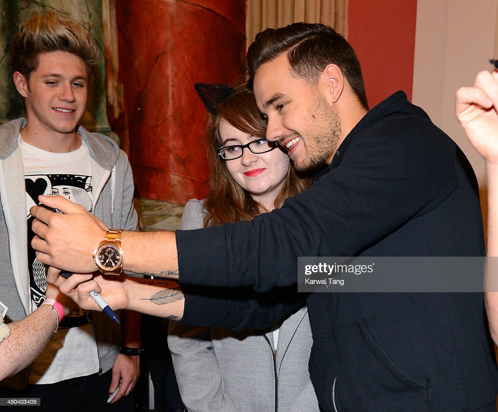 Liam Payne of One Direction poses for a picture with a fan as he attends the book signing of One Direction's new book 'Where We Are' held at Alexandra Palace on November 18, 2013 in London, England.