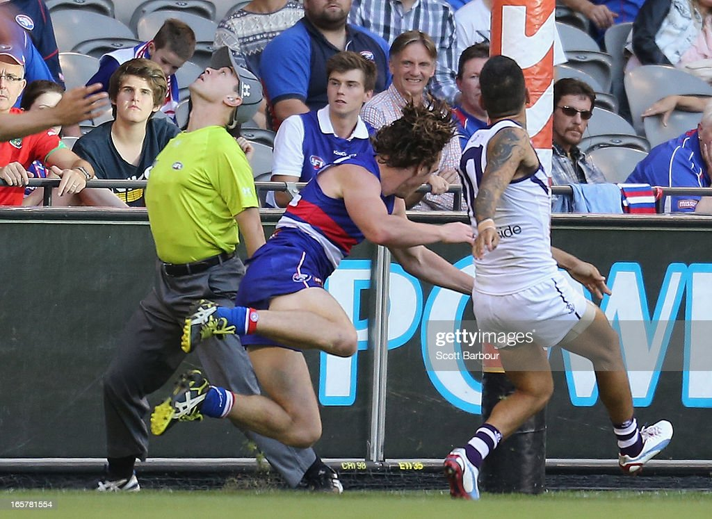Liam Picken of the Bulldogs collides with goal umpire Courtney Lai during the round two AFL match between the Western Bulldogs and the Fremantle Dockers at Etihad Stadium on April 6, 2013 in Melbourne, Australia.