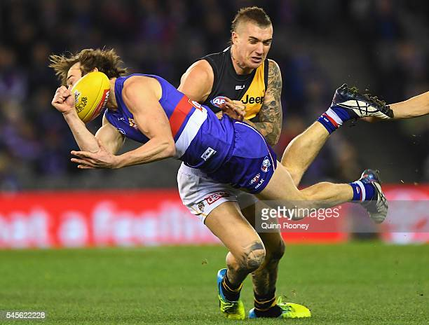 Liam Picken of the Bulldogs handballs whilst being tackled by Dustin Martin of the Tigers during the round 16 AFL match between the Western Bulldogs...