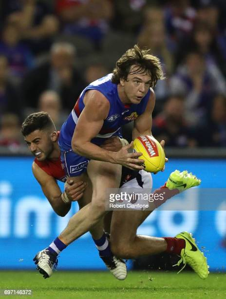 Liam Picken of the Bulldogs is challenged by Christian Salem of the Demons during the round 13 AFL match between the Western Bulldogs and the...