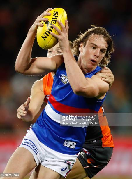 Liam Picken of the Bulldogs is tackled by Devon Smith of the Giants during the 2017 AFL round 06 match between the GWS Giants and the Western...