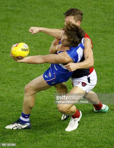 Liam Picken of the Bulldogs is tackled by Jake Melksham of the Demons during the 2017 AFL round 13 match between the Western Bulldogs and the...