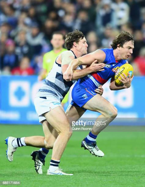 Liam Picken of the Bulldogs is tackled by Jed Bews of the Cats during the round nine AFL match between the Geelong Cats and the Western Bulldogs at...