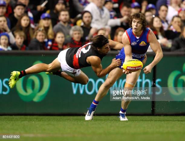 Liam Picken of the Bulldogs is tackled by Mark Baguley of the Bombers during the 2017 AFL round 19 match between the Western Bulldogs and the...