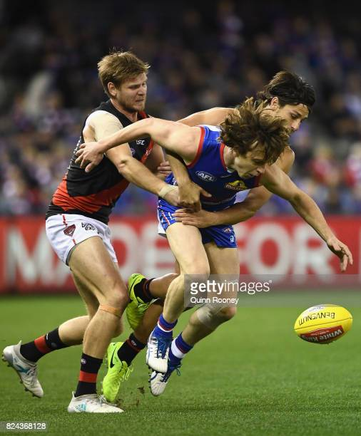 Liam Picken of the Bulldogs is tackled by Michael Hurley and Mark Baguley of the Bombers during the round 19 AFL match between the Western Bulldogs...