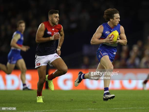 Liam Picken of the Bulldogs runs with the ball during the round 13 AFL match between the Western Bulldogs and the Melbourne Demons at Etihad Stadium...