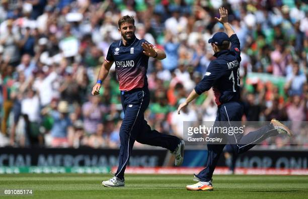 Liam Plunkett of England celebrates with Eoin Morgan after dismissing Imrul Kayes of Bangladesh during the ICC Champions Trophy group match between...